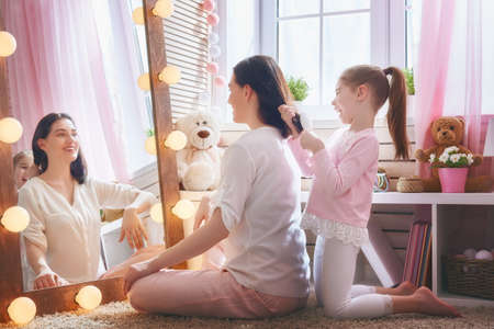Foto per Happy loving family. Cute little girl is combing her mother's hair sitting near mirror in the children room. - Immagine Royalty Free