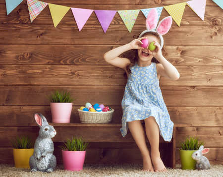 Photo for Cute little child wearing bunny ears on Easter day. Girl holding basket with painted eggs. - Royalty Free Image