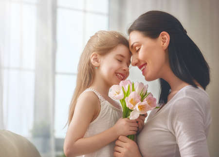 Foto de Happy mother's day! Child daughter congratulates mom and gives her flowers tulips. Mum and girl smiling and hugging. Family holiday and togetherness. - Imagen libre de derechos