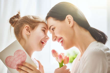 Foto de Happy mother's day! Child daughter congratulates mom and gives her flowers tulips and postcard. Mum and girl smiling and hugging. Family holiday and togetherness. - Imagen libre de derechos