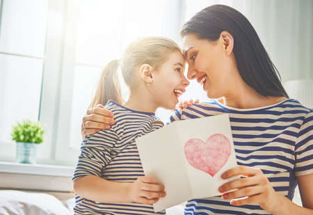 Foto de Happy mother's day! Child daughter congratulates mom and gives her postcard. Mum and girl smiling and hugging. Family holiday and togetherness. - Imagen libre de derechos