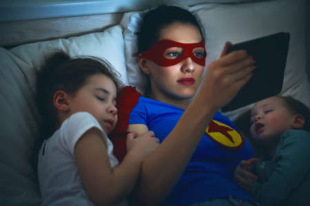 Photo for Adorable little children girls are napping in the bed with their mom. Quiet sleep with teddy bear under the protection of the mother superhero. - Royalty Free Image