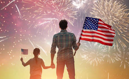 Photo pour Patriotic holiday. Happy kid, cute little child girl and her father with American flag. USA celebrate 4th of July. - image libre de droit