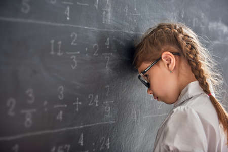 Foto de Tough day at school! Sad child near the blackboard indoors. Kid is learning in class. Complex math, arithmetic and examples. Numbers written with chalk on board. - Imagen libre de derechos