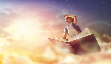 Foto de Back to school! Happy cute industrious child flying on the book on background of sunset sky. Concept of education and reading. The development of the imagination. - Imagen libre de derechos