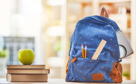 Foto de Back to school and happy time! Apple, pile of books and backpack on the desk at the elementary school. - Imagen libre de derechos