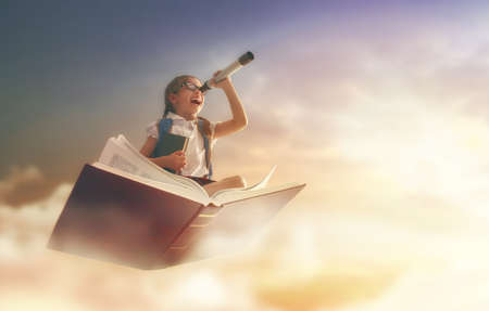 Photo pour Back to school! Happy cute industrious child flying on the book on background of sunset sky. Concept of education and reading. The development of the imagination. - image libre de droit