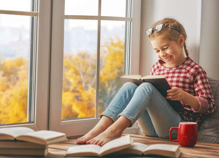Photo for Cute child girl sitting by the window and reading a book in room at home. Beautiful autumn nature. - Royalty Free Image