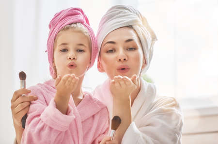 Foto de Happy loving family. Mother and daughter are having fun. Mom and child girl are in bathrobes and with towels on their heads. - Imagen libre de derechos