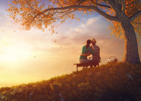 Foto de Happy couple in love. Stunning sensual portrait of young stylish fashion couple picnicking together near a tree in autumn park. - Imagen libre de derechos