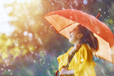 Happy funny child with red umbrella under the autumn shower. Girl is wearing yellow raincoat and enjoying rainfall. Kid playing on the nature outdoors. Family walk in the park.の写真素材