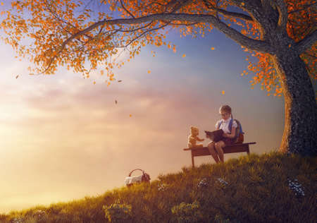 Foto de Back to school! Happy cute industrious child reading the book for her toy near tree on background of sunset. Concept of successful education and reading. - Imagen libre de derechos