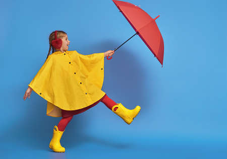 Foto per Happy funny child with red umbrella posing on blue wall background. Girl is wearing yellow raincoat and rubber boots. - Immagine Royalty Free