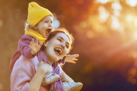 Foto de Happy family on autumn walk! Mother and daughter walking in the Park and enjoying the beautiful autumn nature. - Imagen libre de derechos