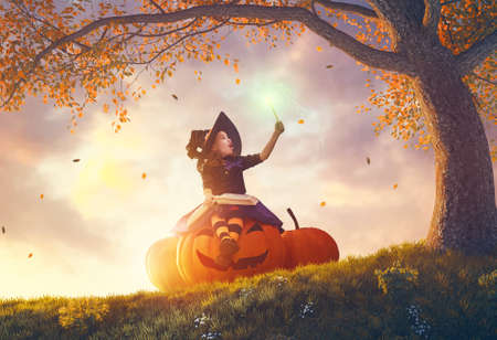 Photo pour Happy Halloween! Cute cheerful little witch with a magic wand and book of spells. Beautiful child girl in costume sitting on the big pumpkin, conjuring and laughing. - image libre de droit