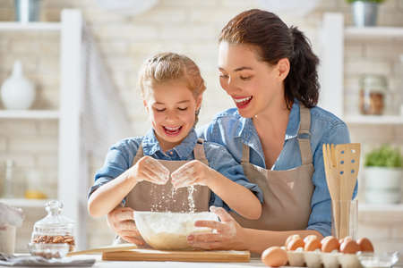 Foto de Happy loving family are preparing bakery together. Mother and child daughter girl are cooking cookies and having fun in the kitchen. Homemade food and little helper. - Imagen libre de derechos