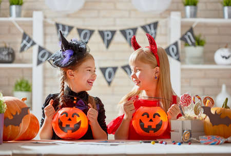 Foto de Cute little children girls with carving pumpkin. Happy family preparing for Halloween. Funny kids at home. - Imagen libre de derechos
