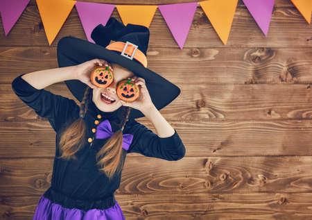 Photo pour Happy Halloween! Cute little witch with cookies pumpkins. - image libre de droit
