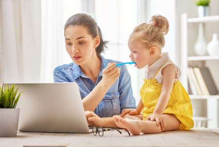 Photo for Young mother with toddler child working on the computer from home. - Royalty Free Image
