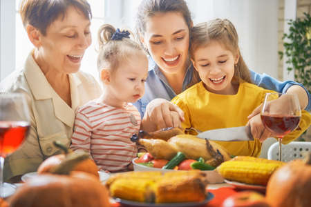 Foto de Happy Thanksgiving Day! Autumn feast. Family sitting at the table and celebrating holiday. Traditional dinner. Grandmother, mother and daughter. - Imagen libre de derechos