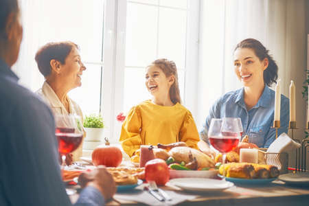 Photo pour Happy Thanksgiving Day! Autumn feast. Family sitting at the table and celebrating holiday. Grandparents, parents and children. Traditional dinner. - image libre de droit