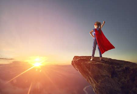 Foto de Little kid is playing superhero. Child on the background of sunset sky. Girl power concept - Imagen libre de derechos