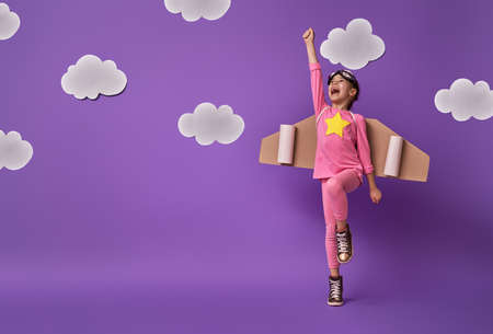 Foto de Little child girl in an astronaut costume is playing and dreaming of becoming a spaceman. Portrait of funny kid on a background of ultraviolet wall with white clouds. - Imagen libre de derechos