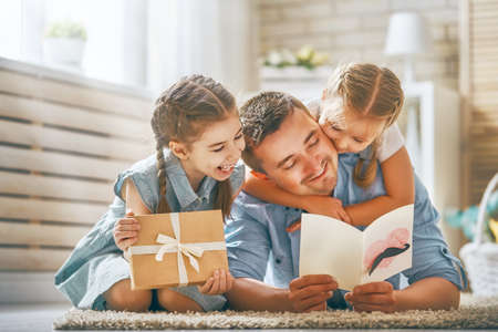 Photo pour Happy father's day! Children daughters congratulating dad and giving him postcard and gift box. Daddy and girls smiling and hugging. Family holiday and togetherness. - image libre de droit