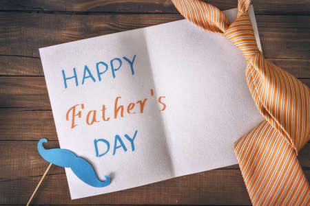 Happy father's day! Postcard and tie on background of wooden table.