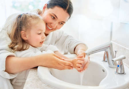 Photo for Cute little girl and her mother are washing hands under running water. - Royalty Free Image