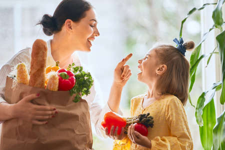 Photo pour Family shopping. Mother and her daughter are holding grocery shopping bag with vegetables. - image libre de droit