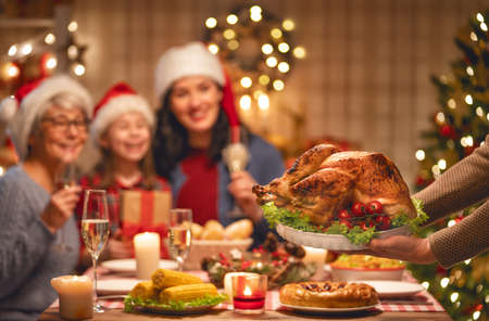 Photo pour Merry Christmas! Happy family are having dinner at home. Celebration holiday and togetherness near tree. - image libre de droit