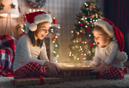 Foto de Merry Christmas and Happy Holiday! Cute little children girls with present gift box near tree at home. - Imagen libre de derechos