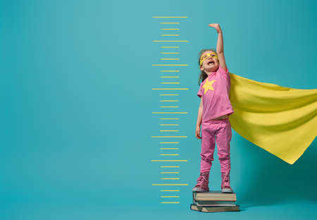 Foto de Little child playing superhero. Kid measures the growth on the background of bright blue wall. Girl power concept. Yellow, pink and  turquoise colors. - Imagen libre de derechos