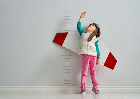 Foto de Little child is playing pilot. Kid is measuring the growth on the background of wall. - Imagen libre de derechos