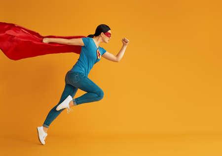 Foto de Joyful beautiful young woman in superhero costume posing on yellow background. - Imagen libre de derechos