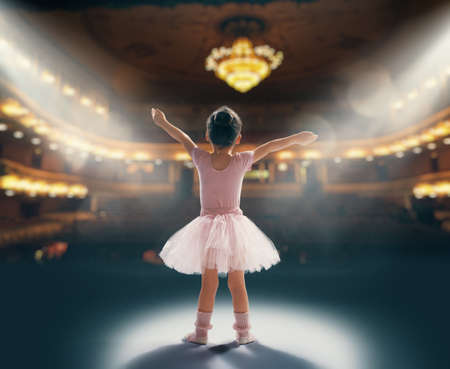 Foto de Cute little girl dreaming of becoming a ballerina. Child girl in a pink tutu dancing on the stage. Baby girl is studying ballet. - Imagen libre de derechos