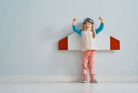 Little child girl in an astronaut costume is playing and dreaming of becoming a spaceman. Portrait of funny kid on a background of grey wall.