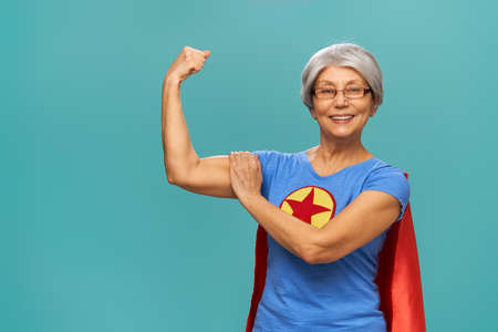 Foto de Joyful beautiful senior woman in superhero costume posing on turquoise background. - Imagen libre de derechos