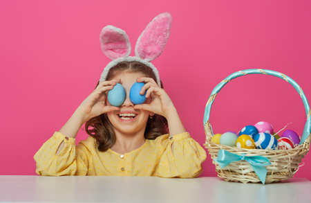 Cute little child wearing bunny ears on Easter day. Girl with painted eggs on bright pink background.