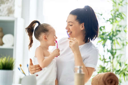 Photo pour Happy family! Mother and daughter child girl are brushing teeth toothbrushes in the bathroom. - image libre de droit