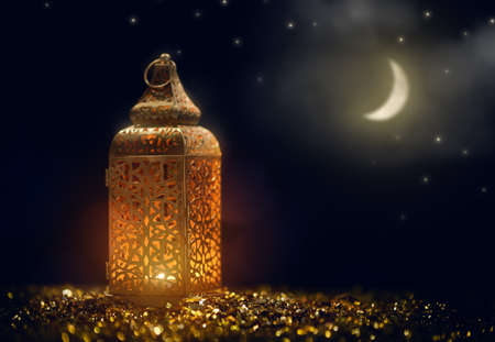 Photo pour Ornamental Arabic lantern with burning candle glowing at night. Festive greeting card, invitation for Muslim holy month Ramadan Kareem.  - image libre de droit