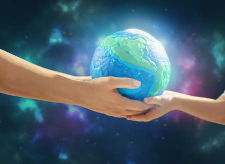 Child and adult holding planet in hands against space background. Earth day holiday concept.