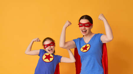 Photo pour Mother and her child playing together. Girl and mom in Superhero costumes. Mum and kid having fun and smiling. Family holiday and togetherness. - image libre de droit