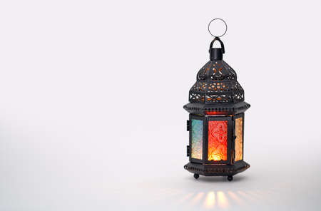 Foto de Ornamental Arabic lantern with burning candle glowing on white background. Festive greeting card, invitation for Muslim holy month Ramadan Kareem. - Imagen libre de derechos