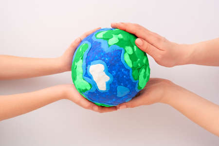 Child and adult holding planet in hands against white background. Earth day holiday concept.