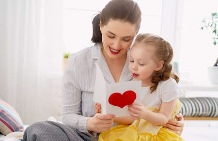 Foto per Happy mother's day! Child daughter is congratulating mom and giving her postcard and gift. Mum and girl smiling and hugging. Family holiday and togetherness. - Immagine Royalty Free