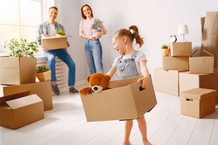 Photo pour Happy young family are moving to new apartment. Parents and daughter with boxes. - image libre de droit