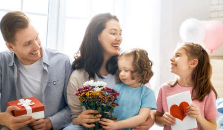 Photo pour Happy mother's day! Children daughters with dad congratulating mom and give her flowers, gift and card. Family holiday and togetherness. - image libre de droit