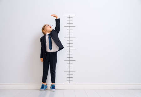Foto de Little child is playing businessman. Kid is measuring the growth on the background of wall. Smart power concept. - Imagen libre de derechos
